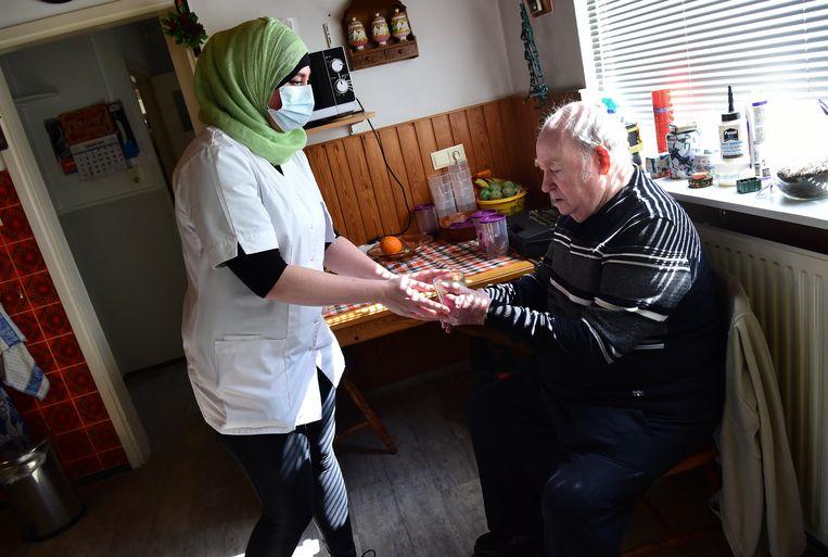 Veel thuiszorgmedewerkers dragen als het kan een mondkapje. Toch vrezen sommigen bij elk huisbezoek: breng ik misschien het virus mee naar binnen? Beeld Marcel van den Bergh / de Volkskrant