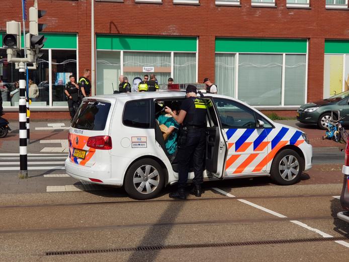 Iemand wordt in een politieauto meegenomen na een schietincident op de Rijswijkseweg in Den Haag.