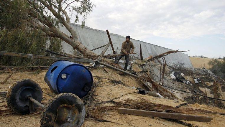 Palestijnen ruimen de schade op na een bomaanslag met Israëlische raketten Beeld EPA