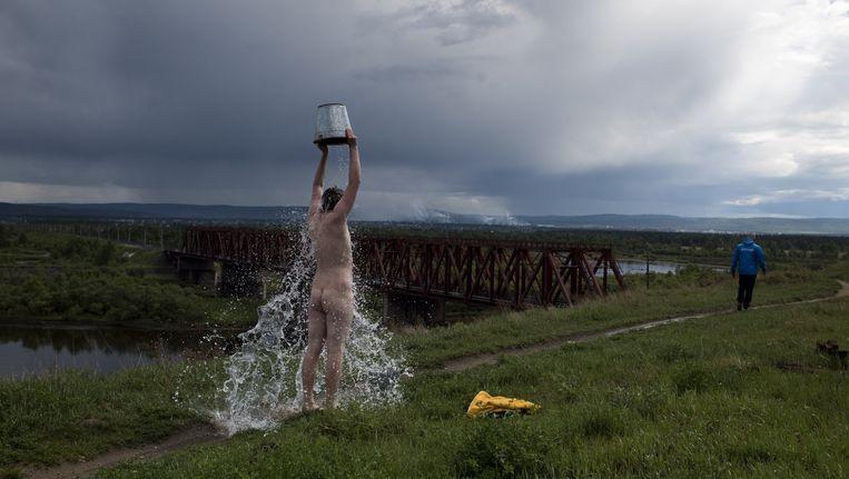 De 17-jarige Dimitri probeert af te kicken in de Volna-kliniek aan de Irkoetrivier. Aan de oever gooit hij een emmer ijskoud water over zich heen. Beeld Yuri Kozyrev