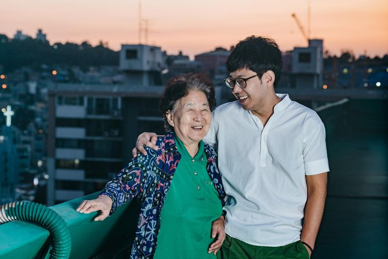 Portret van de Zuid-Koreaanse Kim Okhee (82) en haar kleinzoon Jeon Yongwon (29) op het dak van hun appartement aan de Han rivier in Seoul, Zuid-Korea. Beeld Jun Michael Park
