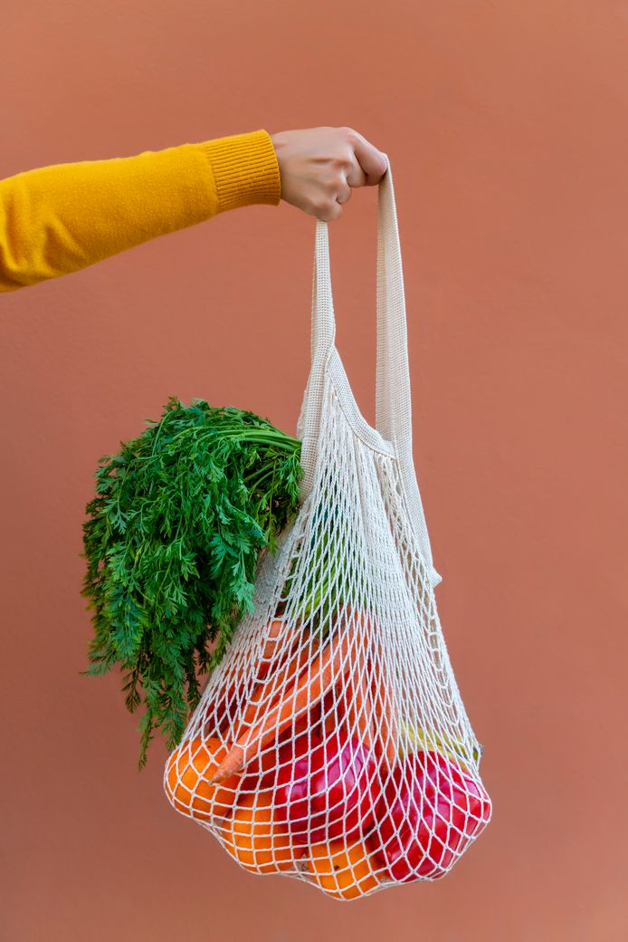Cropped woman hand holding ecologically friendly reusable cotton mesh bag with fruit and vegetables. Zero Waste shopping concept. Salmon color background. boodschappen tas