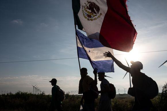 Migranten houden de Mexicaanse en Hondurese vlaggen omhoog tijdens hun voettocht naar de VS.