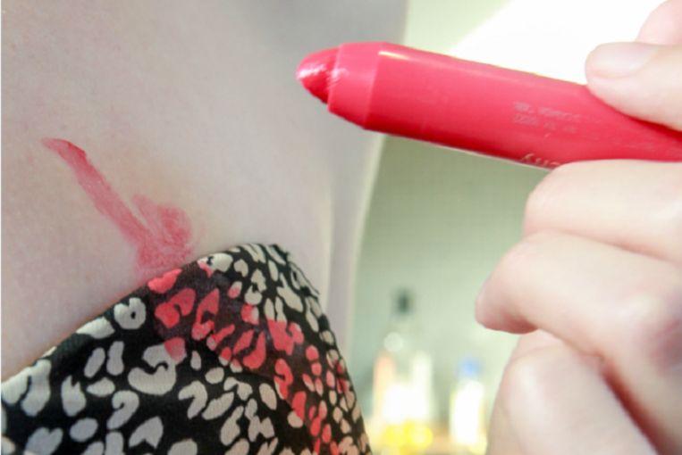 De jumpsuit wordt bewerkt met lipstick...