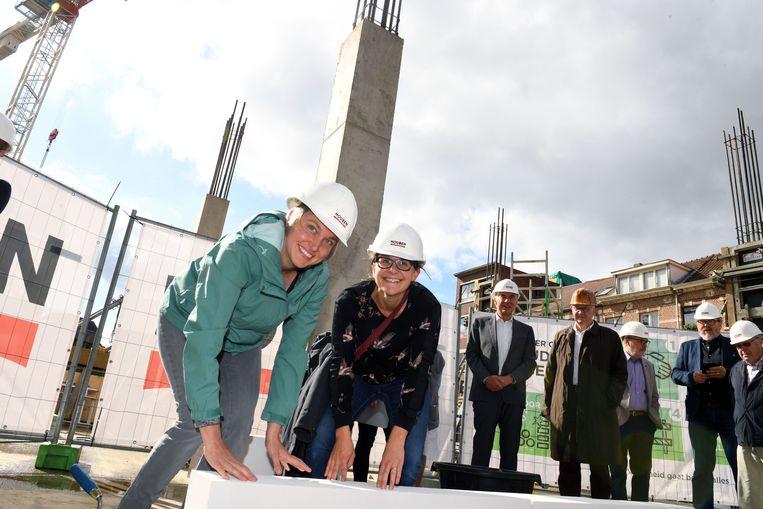 Bieke Verlinden, voorzitter van Zorg Leuven en architecte Elke Martens leggen de eerste steen.