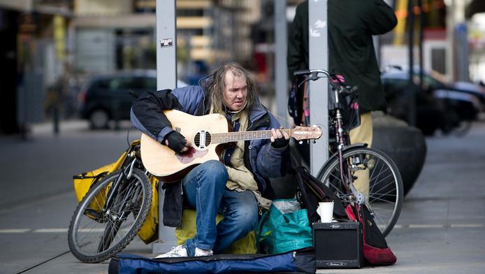 Chuck Deely, de bekendste straatmuzikant van Den Haag, speelt woensdagochtend op zijn gitaar bij het ministerie van VROM en Den Haag Centraal