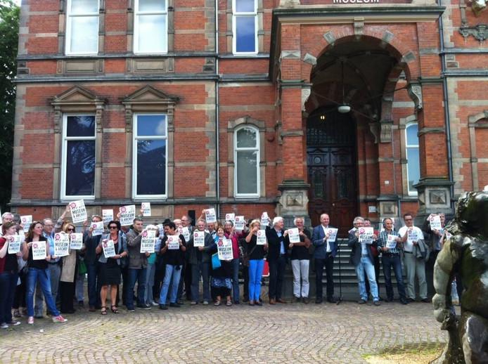 Zo'n zeventig belangstellenden bij de actie voor behoud Jan Cunen houden een protestposter op