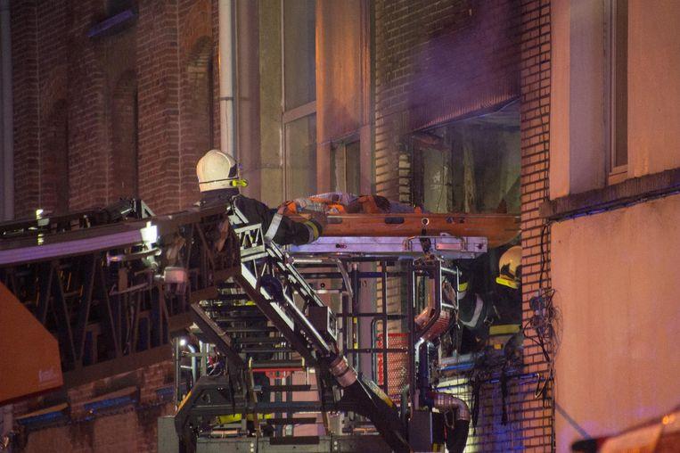 Brandweermannen evacueren met de brandladder een slachtoffer uit het raam.