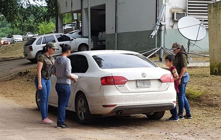 De vrouw (tweede van links) en haar zoontje worden door de politie begeleid terwijl ze naar haar ouderlijk huis gaan.