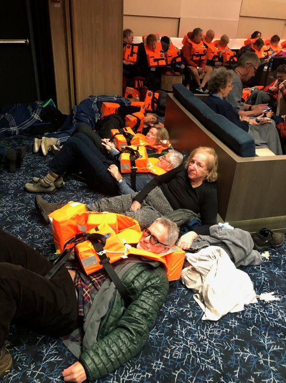 Passagiers wachten met hun reddingsvesten aan in de gang op hun evacuatie.