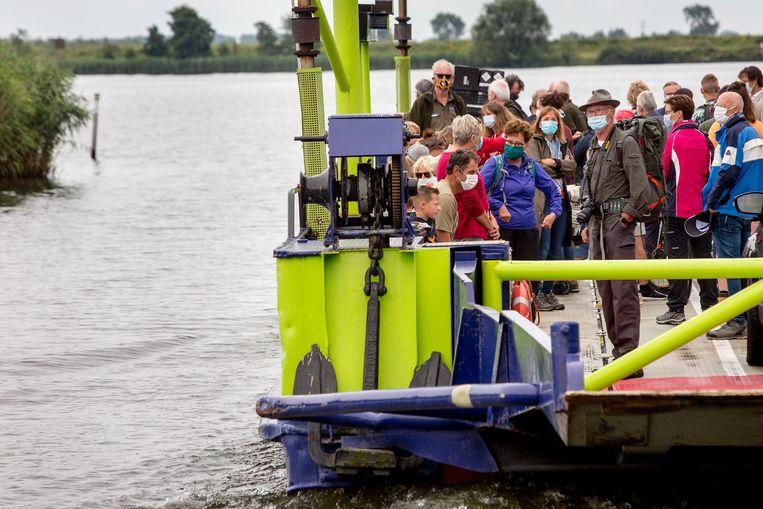 Mensen op de pont naar het eiland Tiengemeten. Beeld Arie Kievit