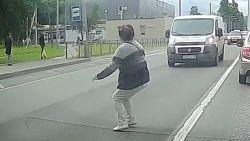 Vrouw steekt straat over zonder te kijken