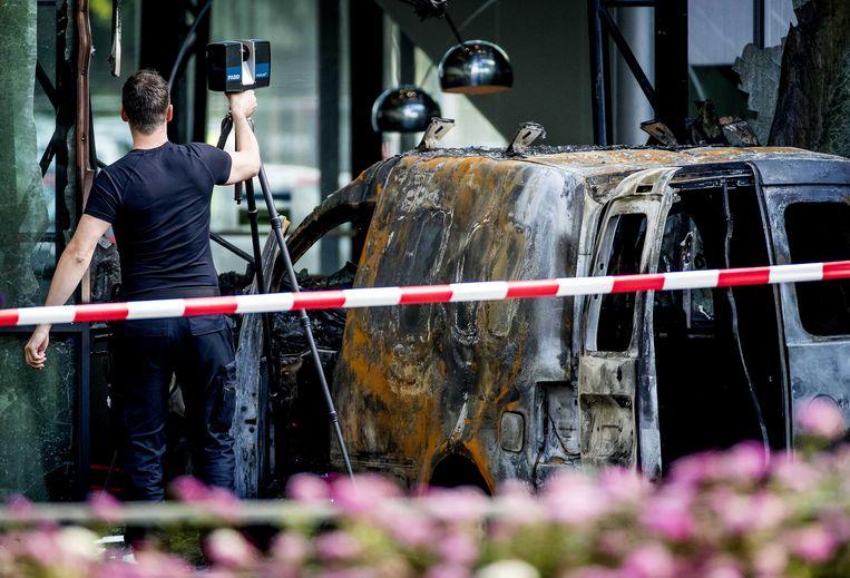 Archieffoto van de bestelauto die met flinke snelheid door de glazen pui van het hoofdkantoor van De Telegraaf is gereden. Na de botsing met de gevel vloog de auto in brand.  Beeld ANP