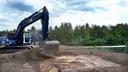 Vrachtwagens en een graafmachine zijn aan het werk om het terrein bouwrijp te maken voor de tweede nieuwbouw op De Meeten II in Roosendaal.