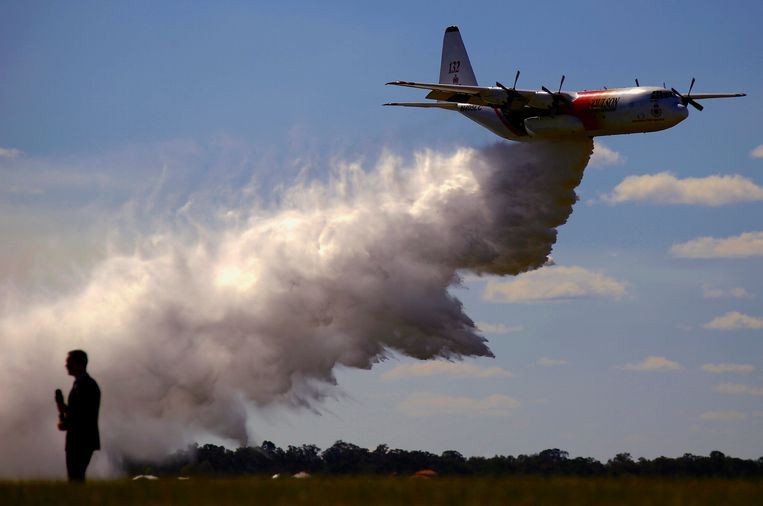 Een C-130 Hercules blusvliegtuig van de Rural Fire Service in New South Wales dropt een lading bluswater. Eenzelfde toestel is vandaag gecrasht in de staat. Daarbij kwamen drie mensen om het leven.