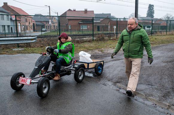 Senne Wijnen met z'n papa Valentin en z'n go-cart op ronde in de buurt om zwerfvuil dat op de straten achtergelaten wordt op te ruimen. Sneeuw en koude houden hem niet tegen.