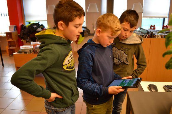 Met de tablet in de hand gaan de kinderen op ontdekking in de bib.