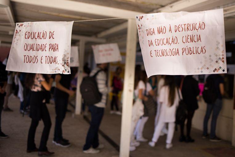 """""""Kwaliteitsonderwijs voor iedereen"""" en """"Zeg 'nee' tegen de vernietiging van educatie, wetenschap, en publieke technologieën"""" staat geschreven op posters gemaakt door studenten aan de Universiteit van Juiz de Fora.  Beeld Valda Nogueira"""