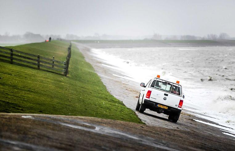 Een auto van Wetterskip Fryslan op een dijk bij Lauwersoog.  Beeld null