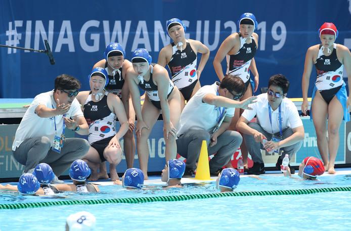 De coach van Zuid-Korea geeft zijn ploeg aanwijzingen.
