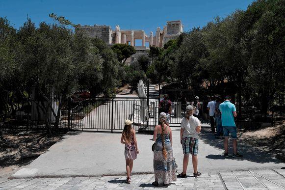 Toeristen voor een gesloten poort aan de Akropolis in Athene vandaag.