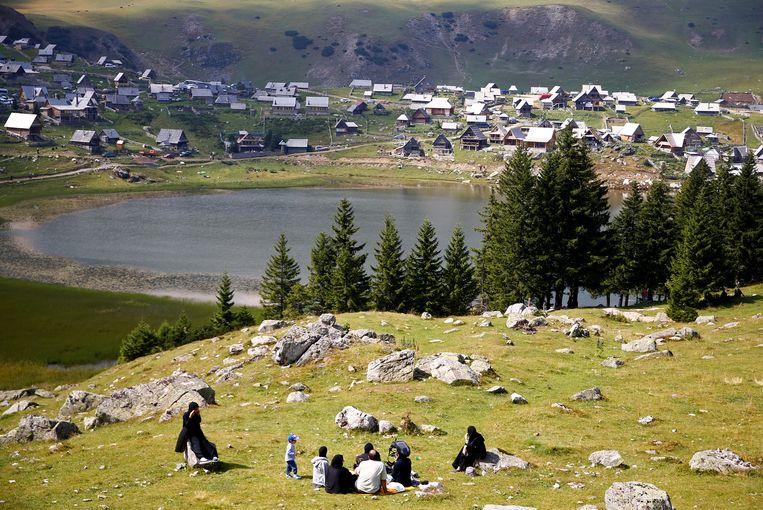 Toeristen uit het Midden-Oosten ontspannen bij een meertje in Bosnië. Beeld REUTERS