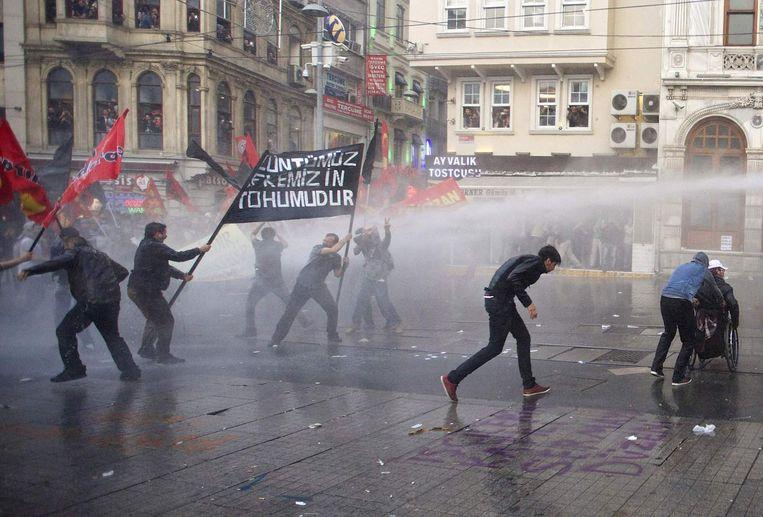 Betogers in Istanboel zoeken dekking voor de waterkanonnen van de politie.