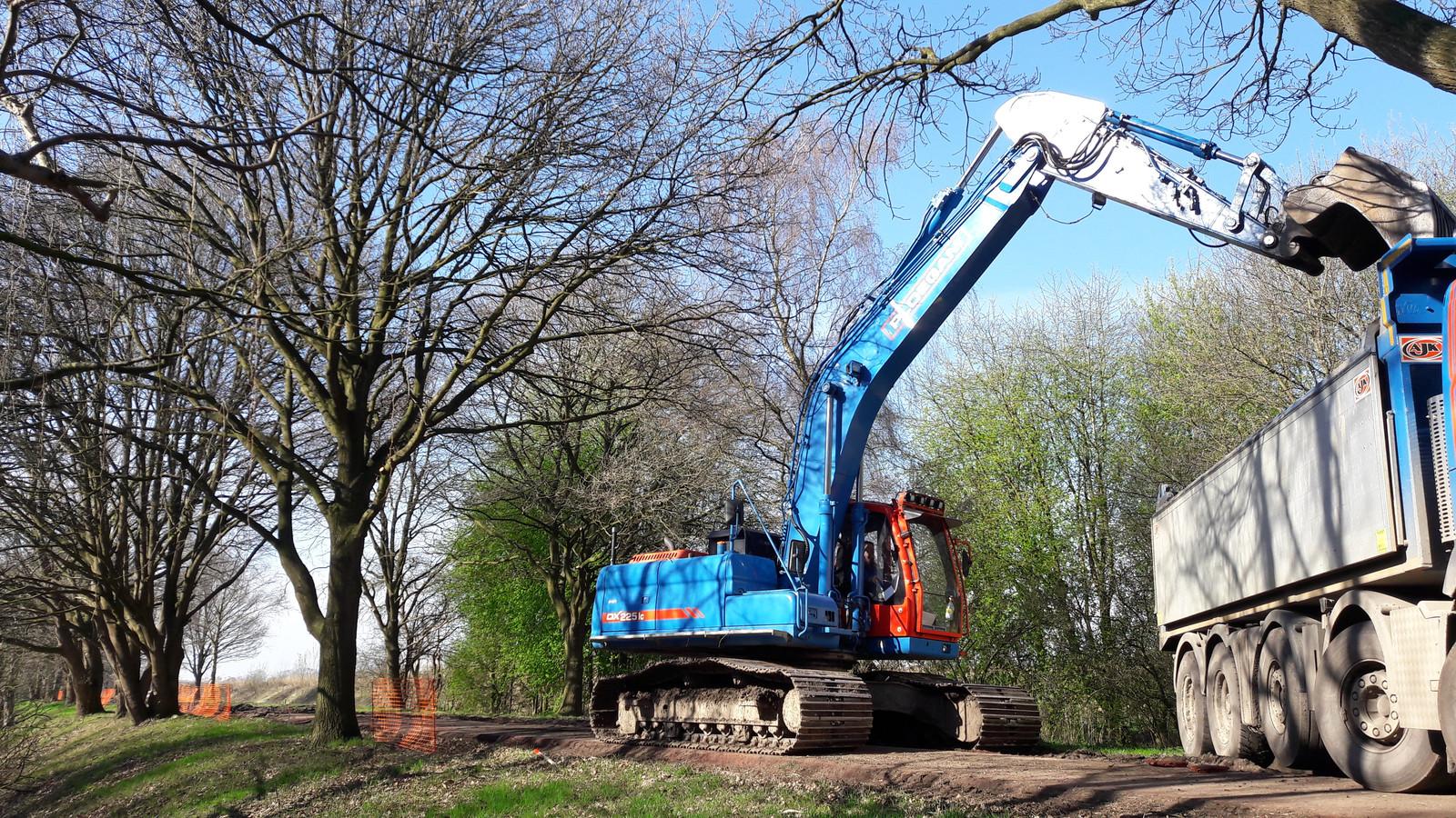 Het eerste stuk van de verbreding in 2017: schep voor schep haalt een graafmachine het asfalt van het Bels Lijntje weg.