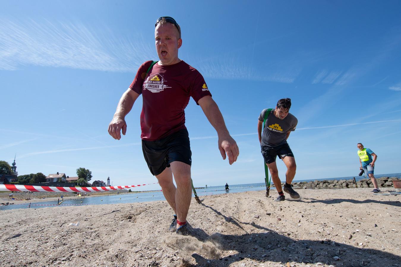Deelnemers aan de Obstacle Challenge op Urk moesten zaterdag onder meer een zware ketting door het water slepen.