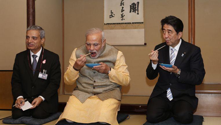 De premiers Modi (midden) en Abe (rechts) eten een hapje in een theehut in Tokyo. Beeld Yuya Shino / AP