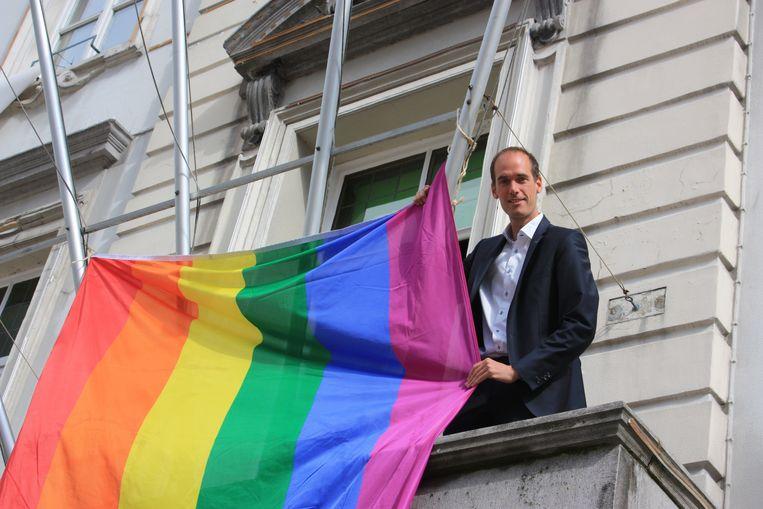 Burgemeester Jenne De Potter hangt de regenboogvlag aan het balkon van het stadhuis.