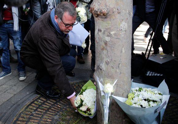 Vertegenwoordiger van de politievakbond Denis Jacob legt bloemen op de plek waar de agent vermoord werd.