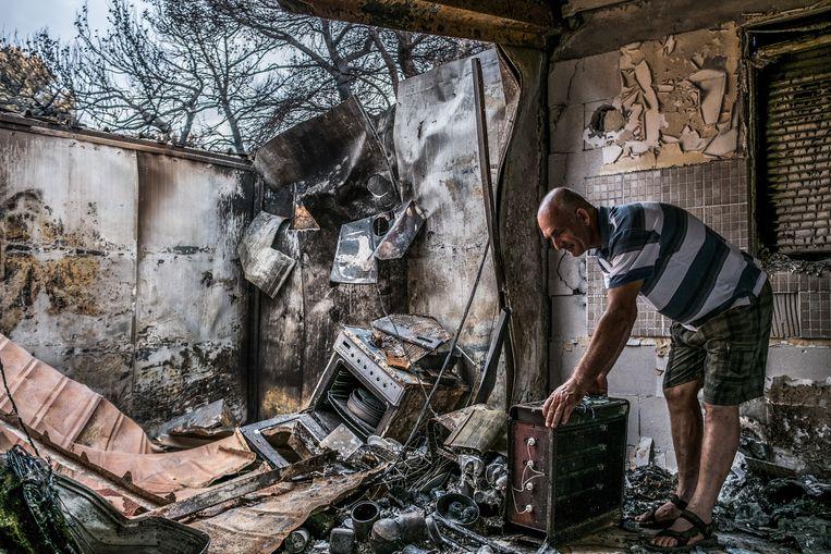 Een Griekse man laat zijn verwoeste huis zien in de badplaats Mati, 30 km ten oosten van Athene. Hoewel de materiële schade voor hem groot is, bleven zijn vijf familieleden ongedeerd. Beeld Joris Van Gennip
