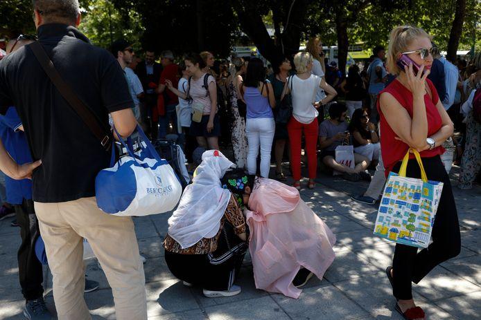 Toeristen hebben zich in veiligheid gebracht en wachten op straat na de aardbeving.