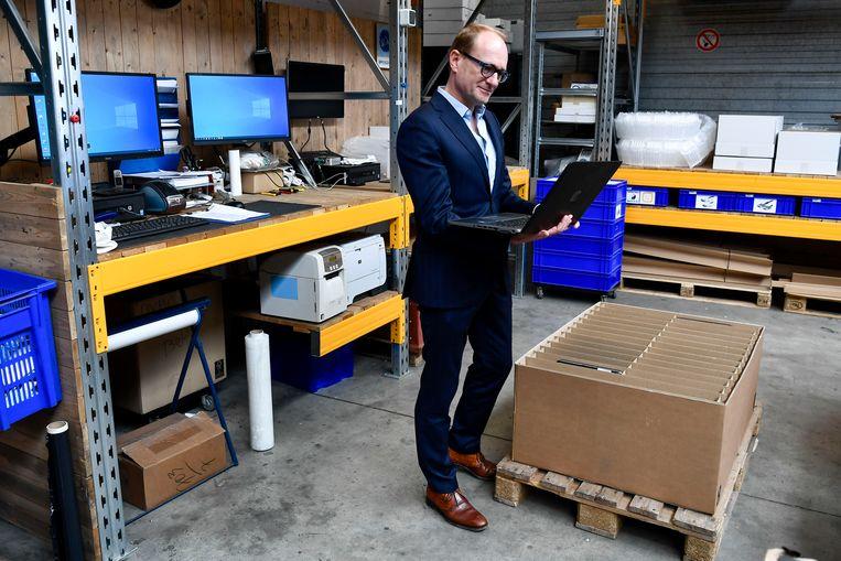 Ben Weyts in een magazijn  waar laptops verzameld worden.