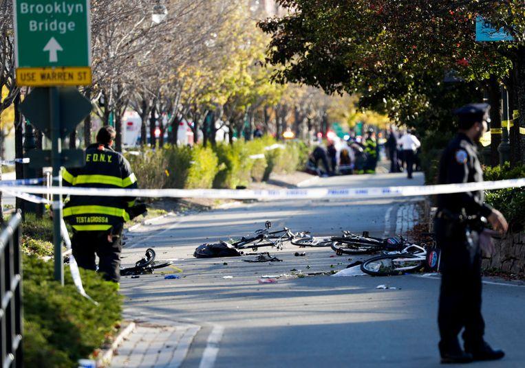 Omvergereden fietsen op een fietspad in New York. In de verte wordt een slachtoffer behandeld. Beeld EPA