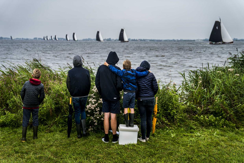 Toeschouwers langs het water bij Sneek tijdens de laatste wedstrijd van het traditionele skutsjesilen in Friesland.