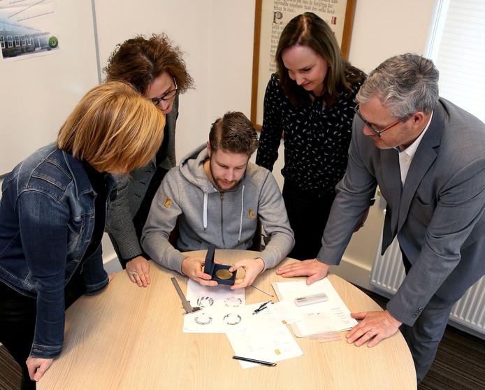 José van Zanten, Ilse Harteman en Brenda Brugman (bestuurssecretariaat) en burgemeester Jan Kottelenberg keuren een proef van de Speld en het Jeugdlintje die zijn ontworpen en uitgevoerd door goudsmid Wilco van den Blink uit Kesteren.