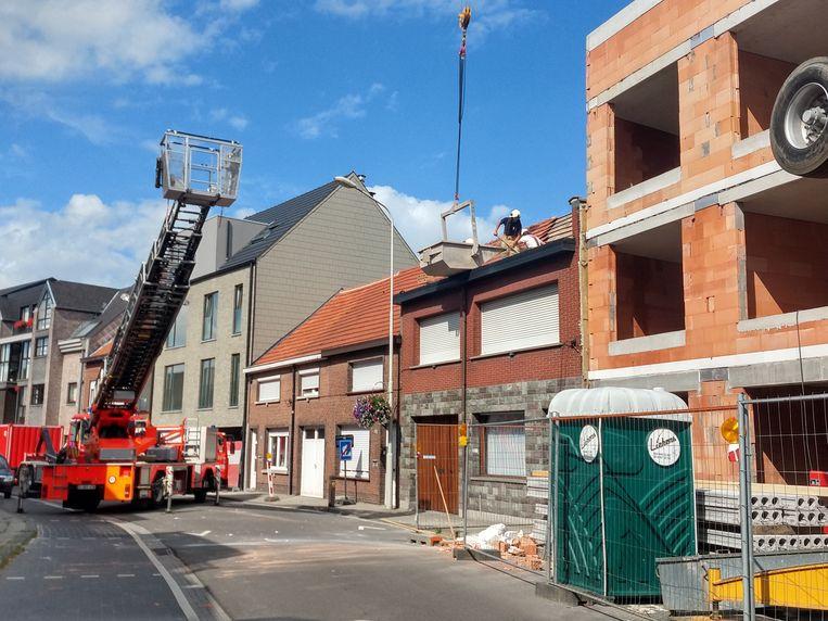 De brandweer aan het werk bij de omgewaaide puntgevel in de Kapellestraat in Aartselaar.