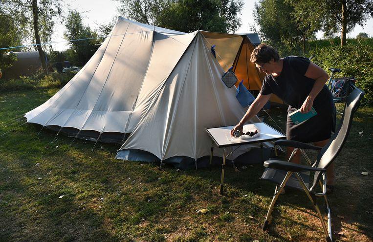 Een kamperende vrouw met een De Waard-tent op natuurcamping De Maasakker in Megen, Noord-Brabant. Beeld Marcel van den Bergh