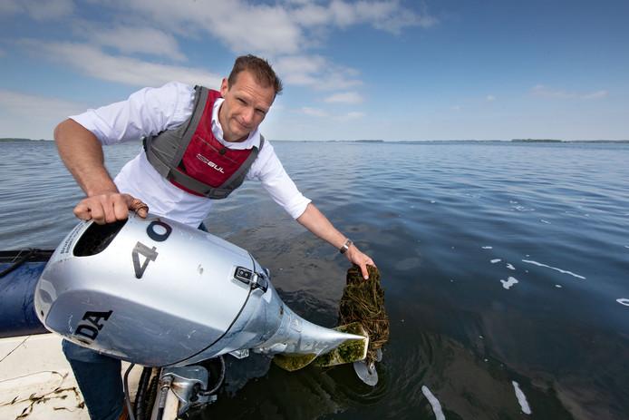 Erik Jeuring van Zeilschool de Randmeren heeft zijn buik vol van woekerende waterplanten.