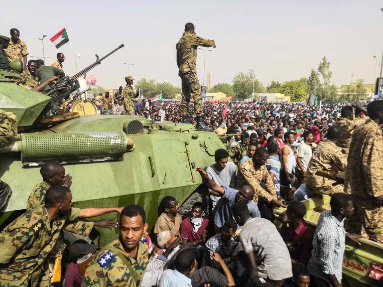 Soldaten en demonstranten in de hoofdstad Khartoem.  De nieuwe militaire machthebbers hebben een dialoog beloofd met de betogers. Beeld AFP