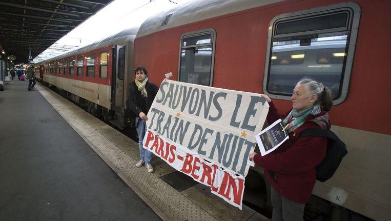 Twee Franse treinliefhebbers proberen Deutsche Bahn nog op andere gedachten te brengen.'Red de nachttrein Parijs-Berlijn', staat er op hun spandoek. Beeld ap