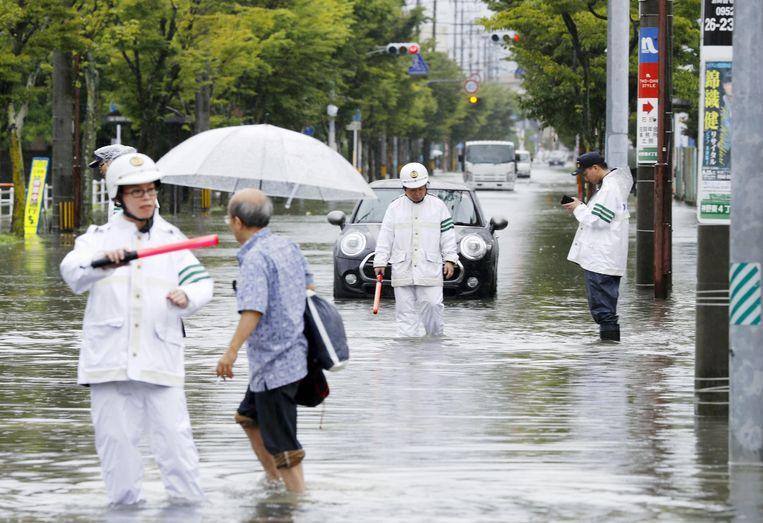 Autoriteiten checken een ondergelopen straat in de stad Saga in het zuiden van Japan.