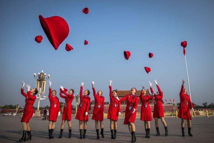 Chinese stewards gooien hun hoeden omhoog op het Tiananmen Plein ter ere van de sluitingsceremonie van het Congres van de Communistische Partij in Peking. Foto Roman Pilipey