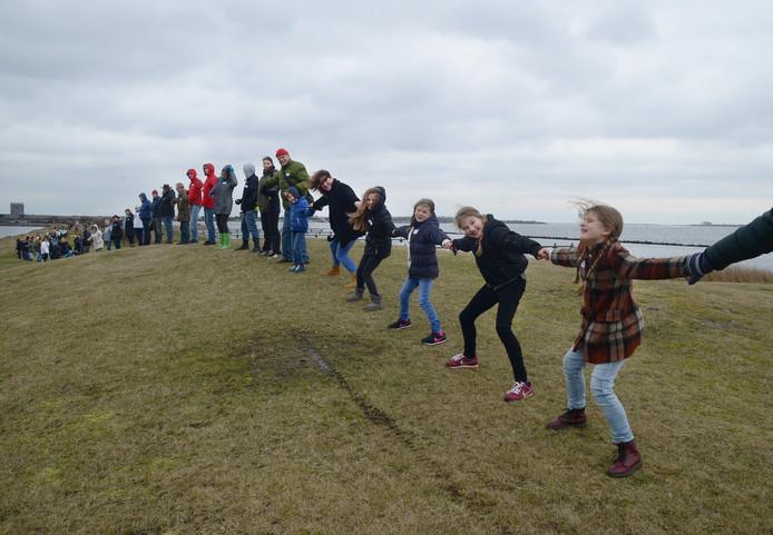 Een menselijk lint over de Middenplaat als actie tegen Brouwerseiland.