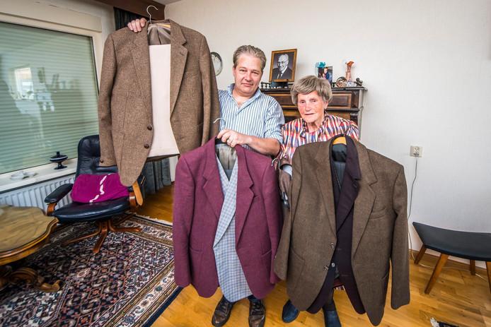 Mevrouw Meijer schenkt tweedelige kostuums van haar overleden man aan de Stichting Help Anderen. Martin Weijermars neemt ze in ontvangst.