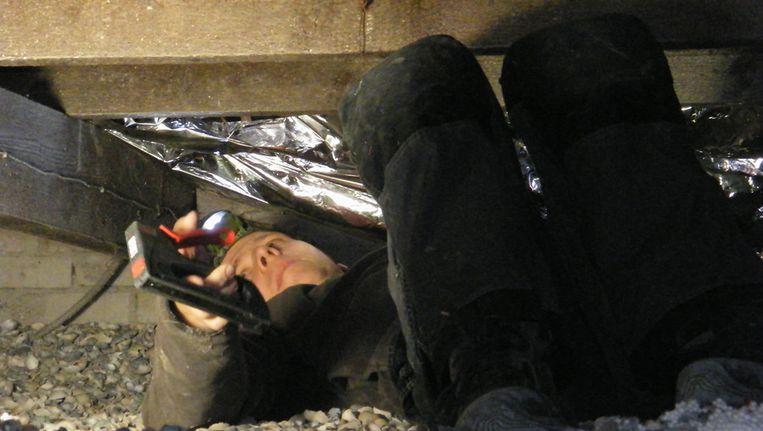 Guido Heidendal bevestigt de isolatiefolie onder mijn woonkamervloer. Beeld Vincent Dekker