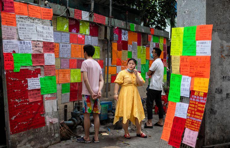 In China zorgen buitenlandse bedrijven voor veel werkgelegenheid. In de stad Guangzhou (links) hangt een muur vol met aanplakbiljetten met vacatures. Beeld Hollandse Hoogte / EPA