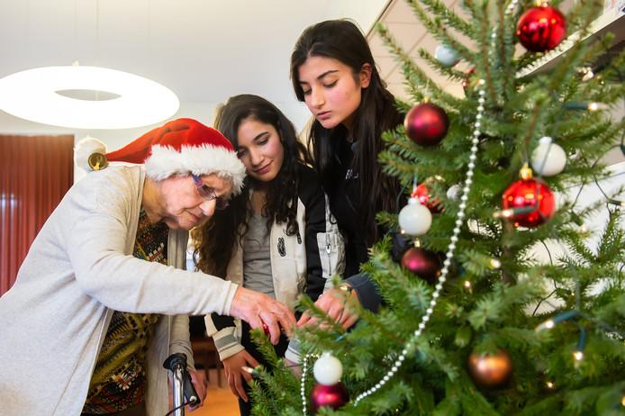 Clasina van Zundert (links) hangt kerstballen in de boom samen met Rouhif Abdo (midden) en Jowana Al haj Rasheed.